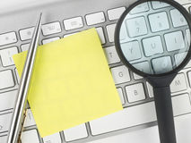 Adhesive note, magnifying glass and pen on keyboard Royalty Free Stock Image