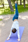 Adho mukha svanasana variation in park alley Royalty Free Stock Images