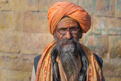 Adhu portrait and close up. The hindu spiritual guide and priest, against ancient stone wall. stock photography