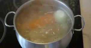 Adição de grãos de pimenta pretos no caldo de carne de cozimento filme