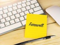 Adiós en nota pegajosa sobre el escritorio del trabajo imagenes de archivo