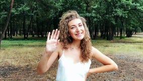 Adiós muestra, sonrisa joven de la mujer y adiós de la demostración con la mano metrajes
