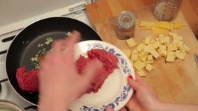 Adición de la carne picadita a la cebolla y al perejil almacen de video