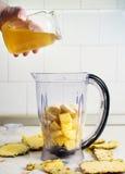 Adición de la miel en una licuadora con la fruta Fotos de archivo