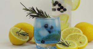 Adici?n de la rama del romero en un vidrio con el c?ctel azul de la limonada de la soda almacen de metraje de vídeo