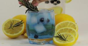Adici?n de la rama del romero en un vidrio con el c?ctel azul de la limonada de la soda metrajes
