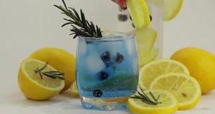 Adición de la rebanada del limón, romero en un vidrio con el cóctel azul de la limonada de la soda almacen de metraje de vídeo