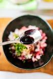 Adición de la salsa de soja a la ensalada de los pescados crudos Fotografía de archivo libre de regalías