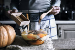 Adición de las especias en el bol de vidrio con en la pasta para la torta de la descarga de la calabaza Fotografía de archivo