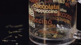 Adición de las hojas de té secas en la taza de cristal Preparación de té verde Cámara lenta Fondo negro almacen de metraje de vídeo