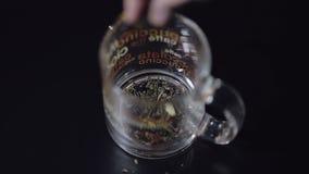 Adición de las hojas de té secas en la taza de cristal Preparación de té verde Fondo negro metrajes