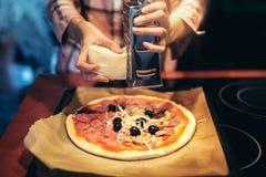 Adición de los ingredientes a la pizza Foto de archivo libre de regalías