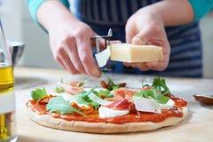 Adición de los ingredientes a la pizza hecha casera Imágenes de archivo libres de regalías