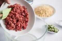Adición de los ingredientes para preparar el kibbeh en un cuenco Fotos de archivo