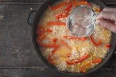 Adición del agua en la cacerola con la opinión superior del arroz y del paprika Foto de archivo libre de regalías