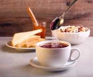 Adición del azúcar en té en una taza Imagen de archivo libre de regalías