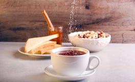 Adición del azúcar en té en una taza Foto de archivo