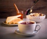 Adición del azúcar en té en una taza Fotos de archivo libres de regalías