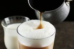 Adición del café al macchiato del latte Foto de archivo libre de regalías