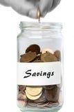Adición del hombre de los ahorros del tarro de las monedas Fotos de archivo