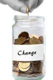Adición del hombre del cambio del tarro de las monedas Fotos de archivo libres de regalías