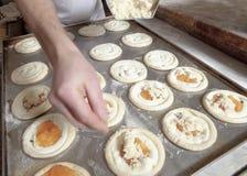 Adición del queso encima de los pasteles antes de cocer Imágenes de archivo libres de regalías