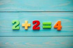 Adición matemática en una superficie de madera Fotografía de archivo