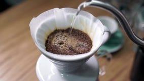 Adicionando a água quente que derrama ao café roasted para o filtro vídeos de arquivo