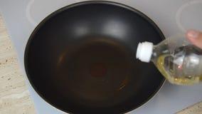 Adicionando o óleo em um frigideira chinesa filme