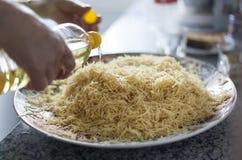 Adicionando o óleo vegetal a uma placa completamente da aletria cozinhada cozinhada foto de stock