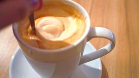 Adicionando o açúcar ao cappuccino e ao stirring Tiro 4K ascendente próximo da xícara de café filme