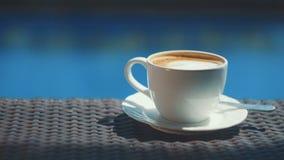 Adicionando o açúcar ao copo do cappuccino na tabela de vime com fundo da água azul video estoque
