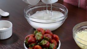 Adicionando o açúcar ao misturar o creme doce Creme de ovo branco de mistura na bacia com misturador do motor filme