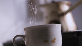 Adicionando o açúcar dentro a um copo de café vídeos de arquivo