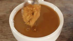 Adicionando o açúcar mascavado a um copo do café do leite video estoque