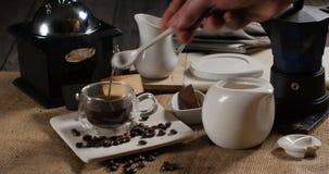 Adicionando o açúcar a uma xícara de café de uma máquina italiana tradicional do café vídeos de arquivo