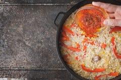 Adicionando o açafrão na bandeja com opinião superior do arroz e de pimenta de sino Fotos de Stock Royalty Free