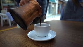 Adicionando o café turco em um copo filme