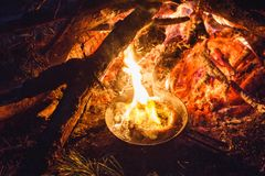 Adicionando salsichas em uma bandeja em um fogo na floresta da noite imagem de stock