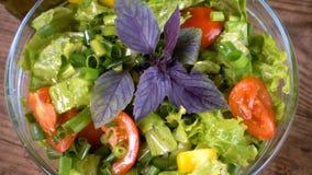 Adicionando uma especiaria da folha da manjericão à salada na bacia de vidro filme