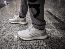 ADIDAS ÖKAR ULTRA, vita och gråa skor på en svart keramisk jordning royaltyfri fotografi