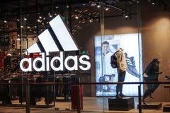 Adidas logo sports retail shop window front. Adidas fashion shop with logo and sign. Adidas sports retail store front in shopping mall China stock photo
