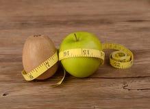 Adiete el concepto, la fruta de kiwi con la manzana verde y a la cinta métrica Foto de archivo
