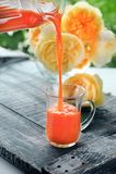 Adiete el jugo de zanahoria fresco vertido de la jarra en la taza de cristal en un fondo de rosas amarillas Copie el espacio Foto de archivo libre de regalías