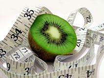 Adiete la fruta (kiwi) con la cinta de la medida Fotografía de archivo