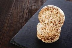 Adiete la pila de las tortas de arroz en el pedazo oscuro de tablero en la tabla de madera, foco selectivo Fotos de archivo libres de regalías