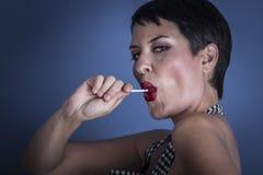 Adiete, mujer joven feliz con el lollypop en su boca en la parte posterior del azul Imagen de archivo libre de regalías