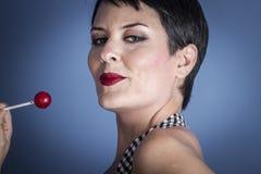 Adiete, mujer joven feliz con el lollypop en su boca en la parte posterior del azul Foto de archivo