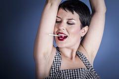 Adiete, mujer joven feliz con el lollypop en su boca en la parte posterior del azul Fotografía de archivo libre de regalías