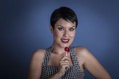 Adiete, mujer joven feliz con el lollypop en su boca en la parte posterior del azul Fotografía de archivo